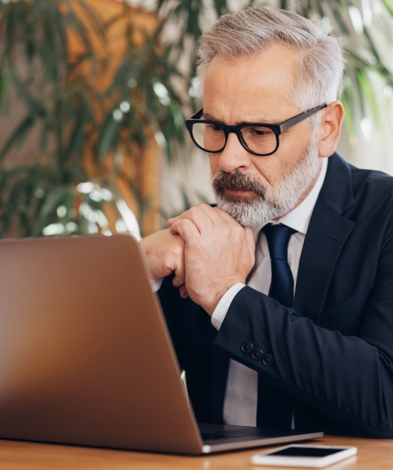 businessman thinking in front of a laptop computer